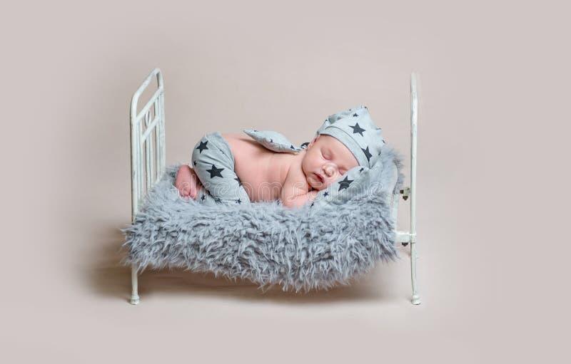 小轻便小床睡觉的甜新出生的男孩 免版税库存图片