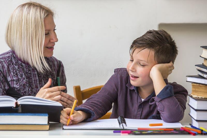 小辈学生在他的家庭教师帮助下做家庭作业 帮助 库存照片