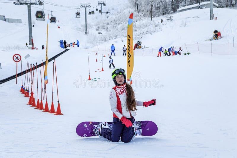 小辈滑雪下坡竞争在高尔基Gorod冬天山滑雪场多雪的倾斜举行  女孩挡雪板跌倒了  库存图片
