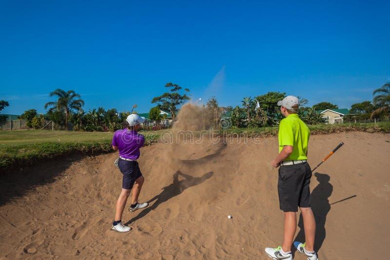 小辈球员沙子射击高尔夫球实践  库存照片