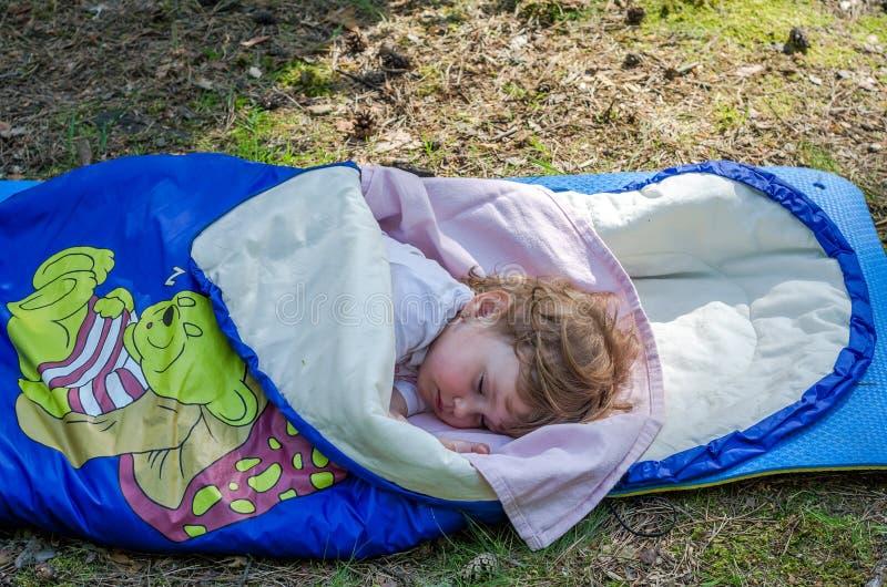 小迷人的女孩婴孩,睡觉在睡袋在野营在地面上附近在森林,有narisovanna睡觉熊的 库存图片