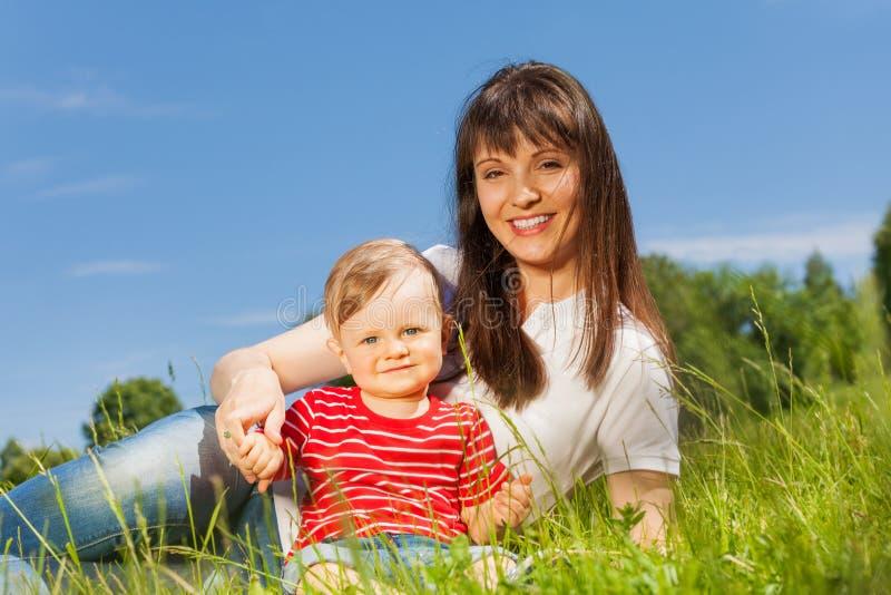 小逗人喜爱的坐在草甸的婴孩和他的妈咪 免版税库存照片