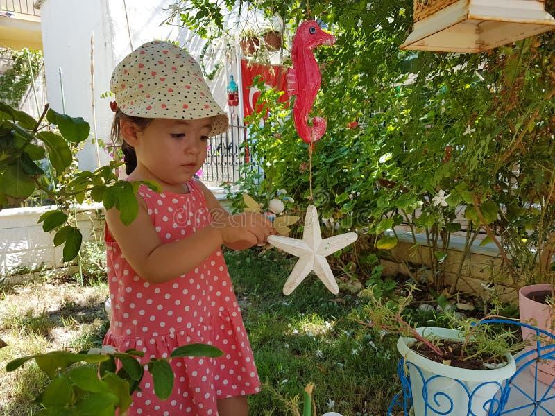小逗人喜爱的女孩使用与在求知欲的庭院玩具 免版税图库摄影