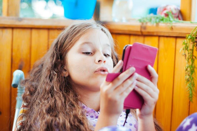 小逗人喜爱的女孩使用与智能手机的,白天,在家 库存图片