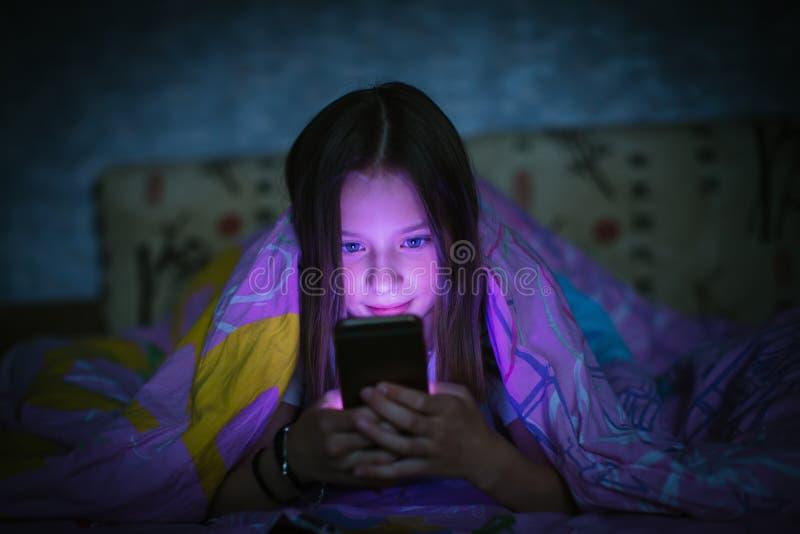 小逗人喜爱的女孩在床上在看智能手机的毯子下的晚上 免版税库存照片