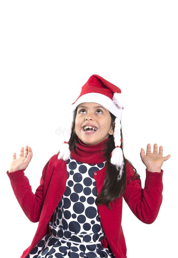 小逗人喜爱的女孩在查寻圣诞老人的帽子复制空间 免版税库存照片