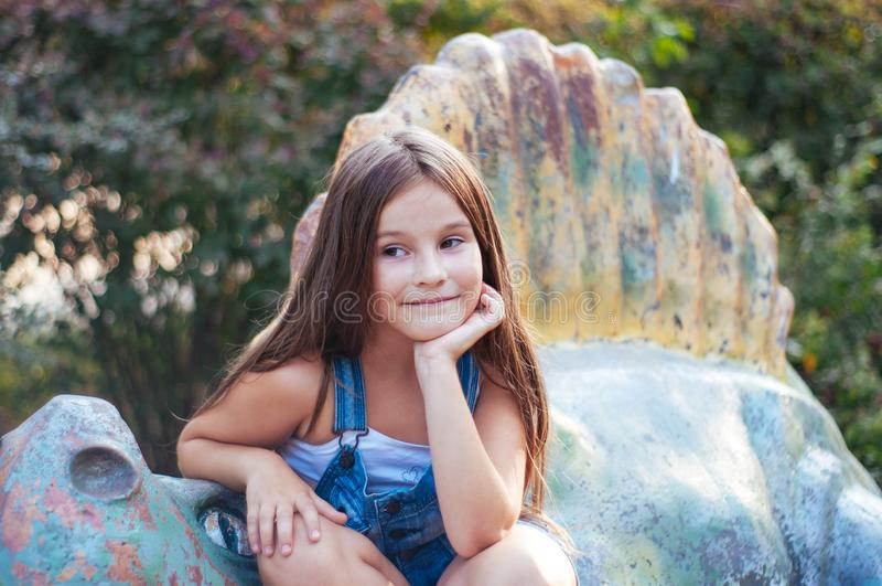 小逗人喜爱的女孩坐恐龙雕象在公园夏天 库存图片