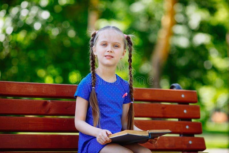 小逗人喜爱的女孩坐长凳和读书 免版税图库摄影