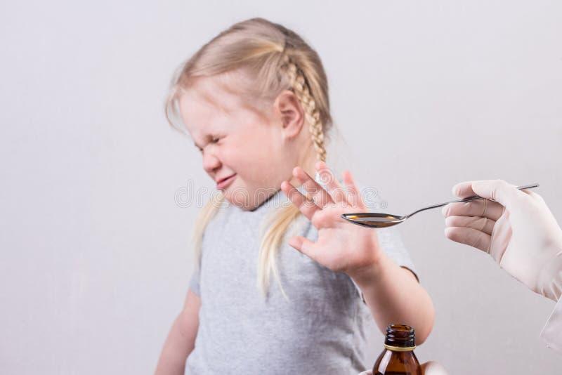 小逗人喜爱的女孩穿上` t要得到医学液体饮用的糖浆匙子  库存照片