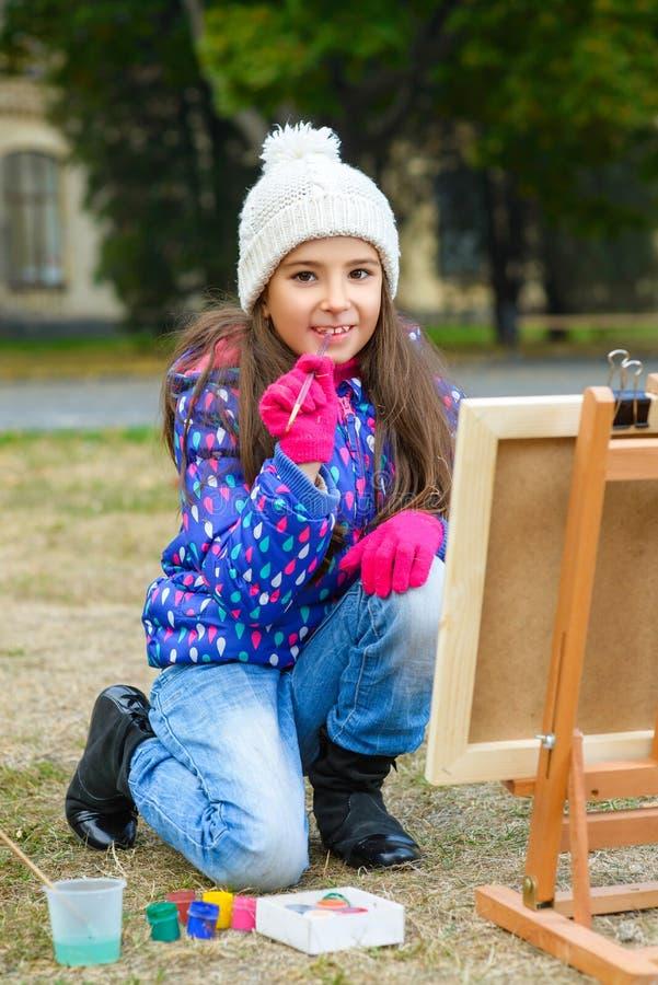小逗人喜爱的女孩画在画架的油漆户外 免版税图库摄影