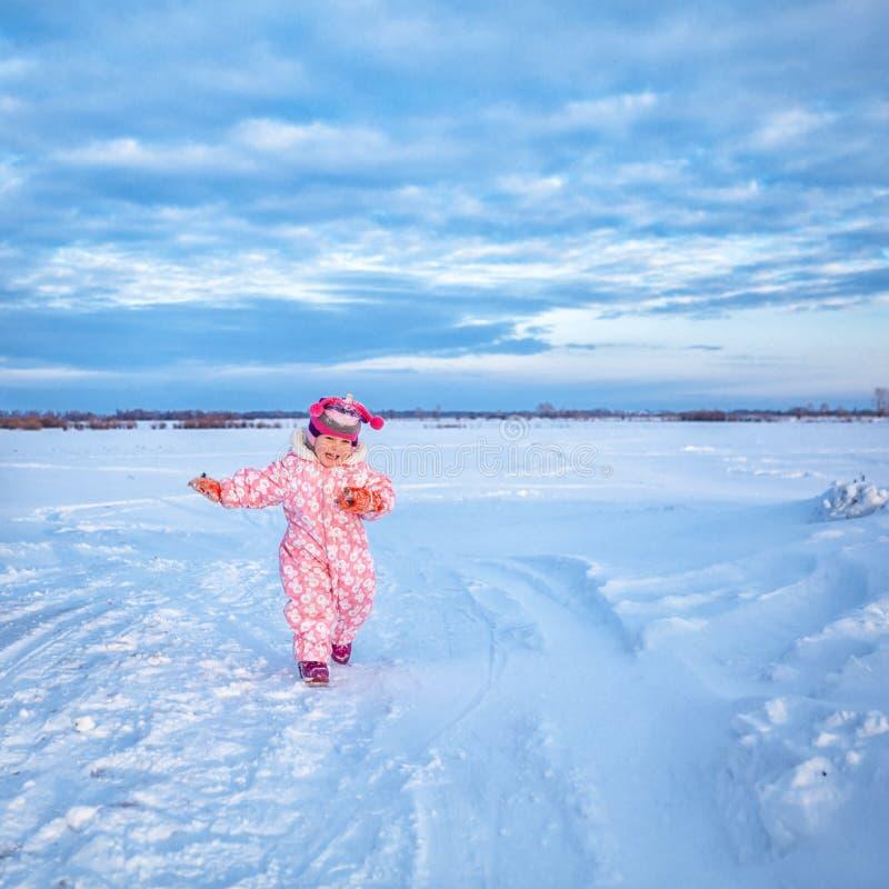 小逗人喜爱的愉快的女婴,步行画象在冬天雪公园, 免版税图库摄影