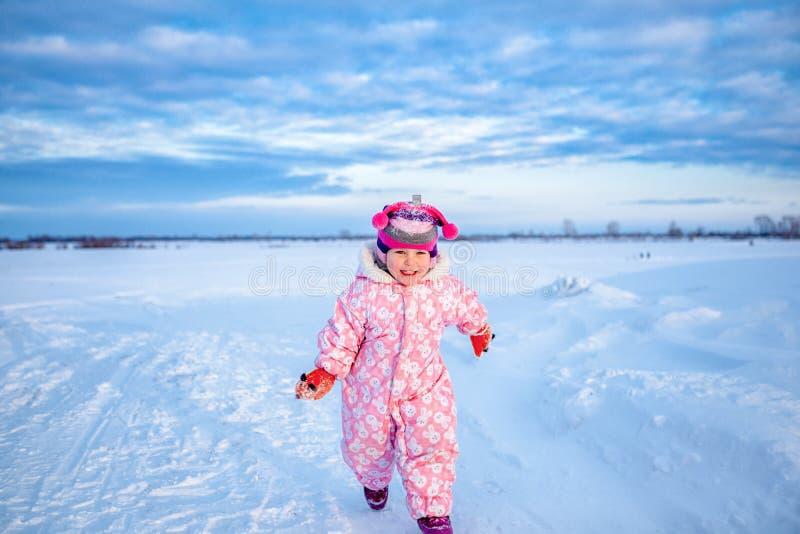 小逗人喜爱的愉快的女婴,步行画象在冬天雪公园, 免版税库存图片