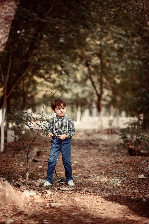 小逗人喜爱的男孩在站立在植物附近的葡萄酒衣裳穿戴了 库存图片
