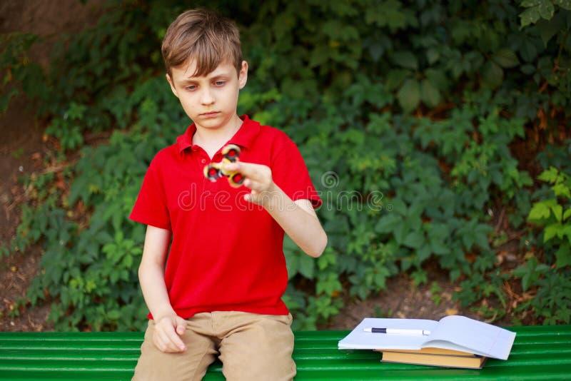 小配件瘾 以后使用与坐立不安锭床工人的男小学生  图库摄影