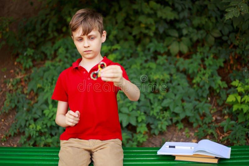 小配件瘾 使用与坐立不安锭床工人的男小学生  库存照片