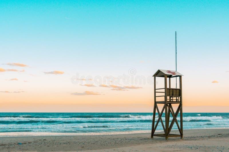 小野鸭和海滩日出橙色心情与葡萄酒救生员木塔的 免版税库存照片