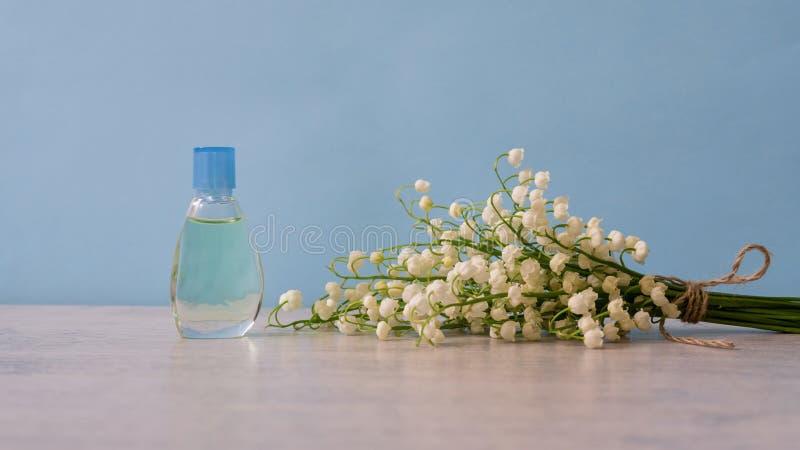 小铃兰花瓶香水和花束在淡色背景的 香料厂,芬芳,化妆用品 免版税库存照片