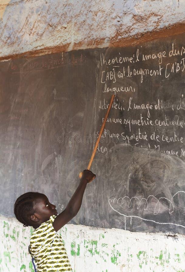 小非洲女孩在运作在锻炼的教室 免版税图库摄影