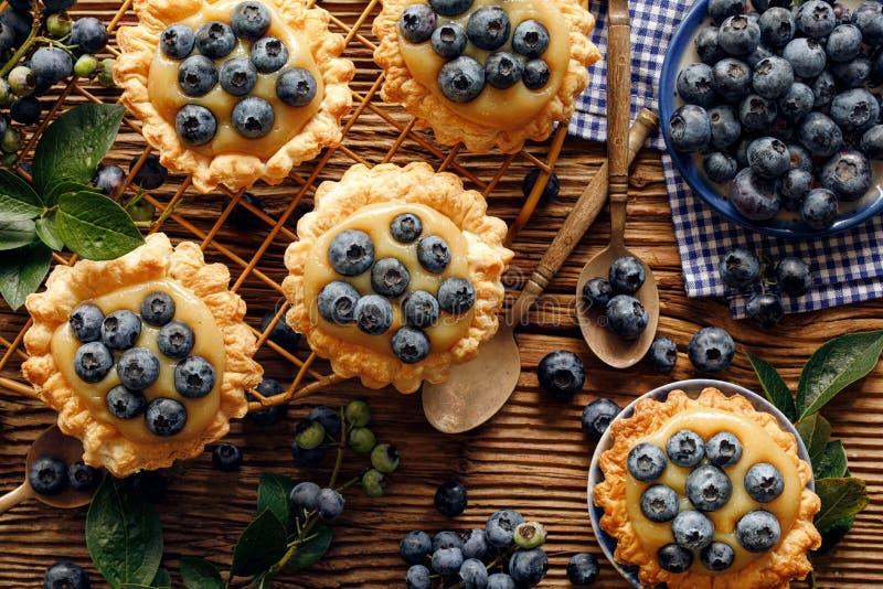 小馅饼做了油酥点心用加法新鲜的蓝莓和焦糖巧克力乳蛋糕在一张木土气桌,顶视图, 免版税库存照片
