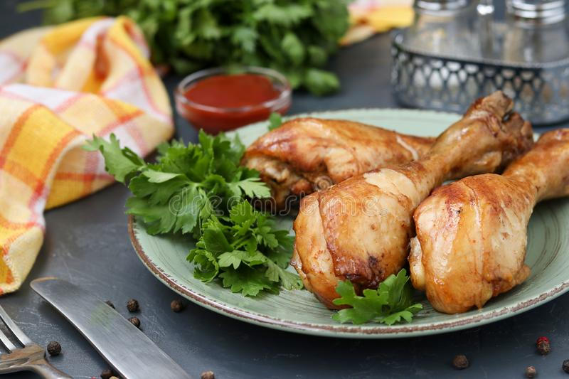 小鸡腿,烘烤在番茄酱、酱油和香醋卤汁在一块板材在黑暗的背景 免版税库存图片