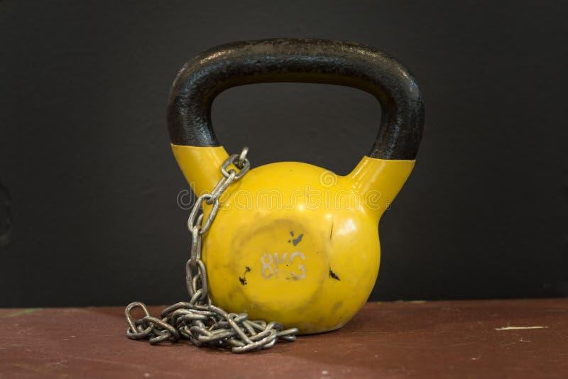 小黄色八公斤与银色链子的重的被用完的kettlebell反对黑背景 健身房和健身设备 库存照片