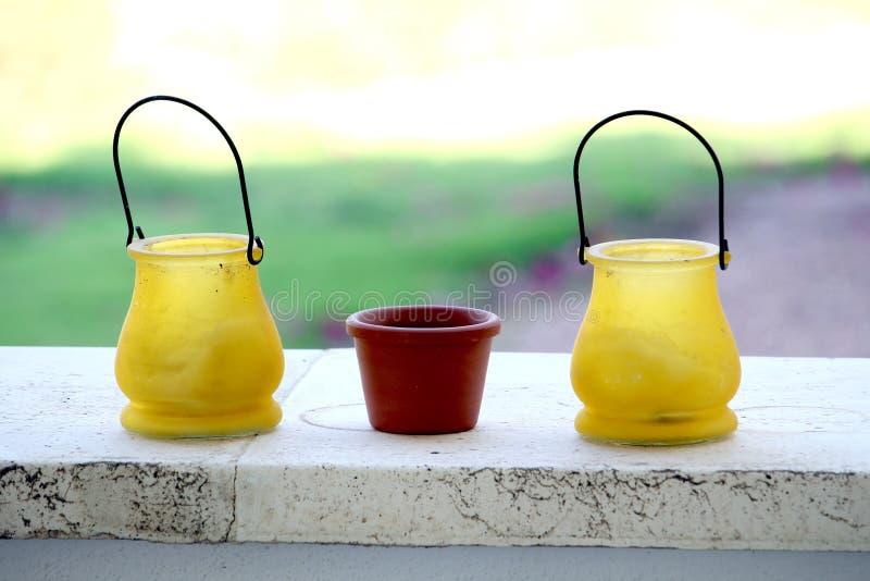 小黄色和赤土陶器罐,在一个石壁架,与明亮 库存照片