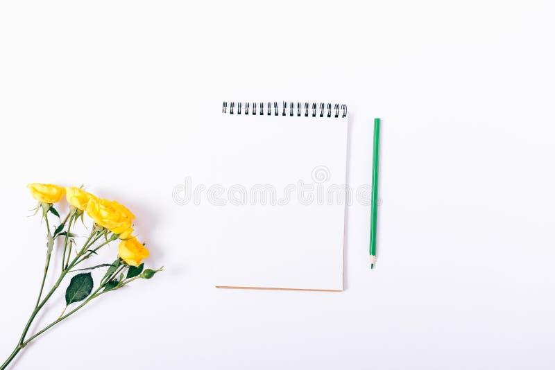 小黄色玫瑰和笔记本有铅笔的 免版税库存图片