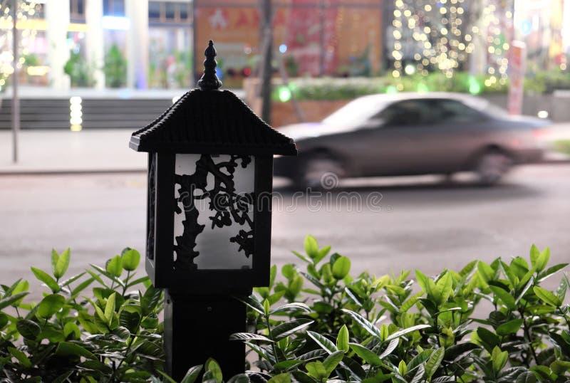 小,美妙地装饰的街灯 美丽的绿色叶子 被弄脏的交通 库存图片