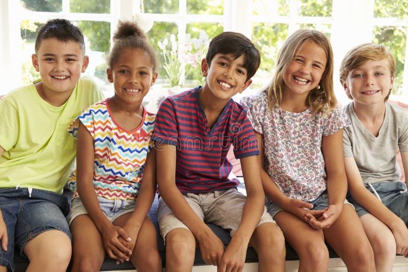 小组一起靠窗座位的多文化孩子 图库摄影