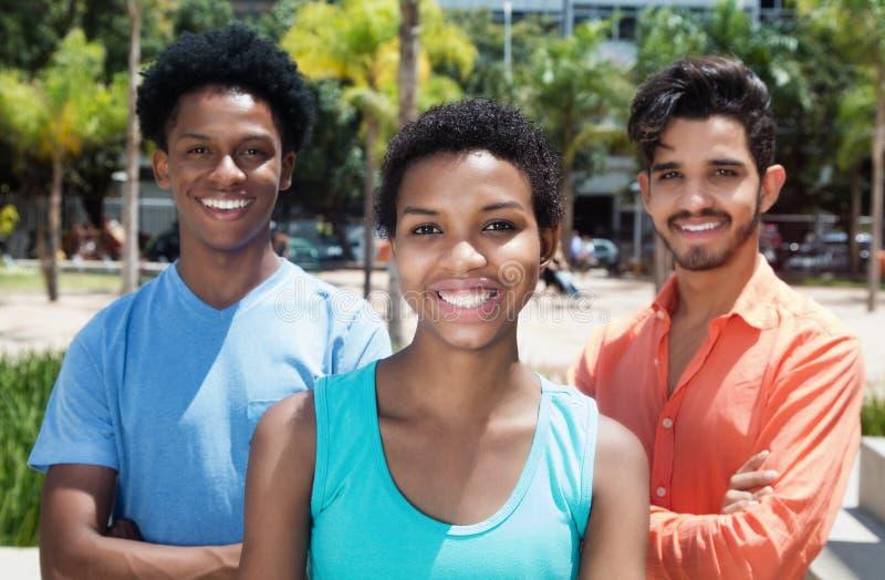小组三个凉快的拉丁美洲的年轻成人在城市 免版税库存图片