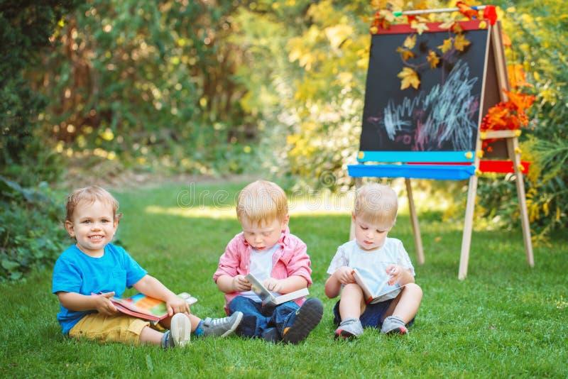 小组三个白白种人小孩孩子哄骗坐外面在夏天秋天公园的男孩和女孩通过画画架 免版税库存照片