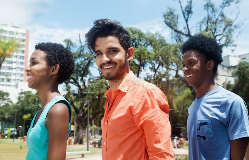 小组三个笑的拉丁美洲的年轻成人在城市 免版税图库摄影