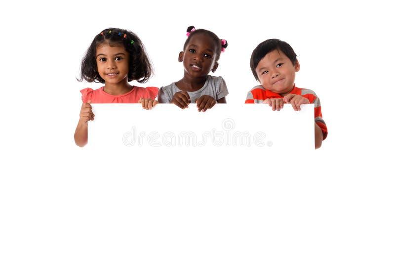 小组与白板的多种族孩子画象 查出 免版税库存照片