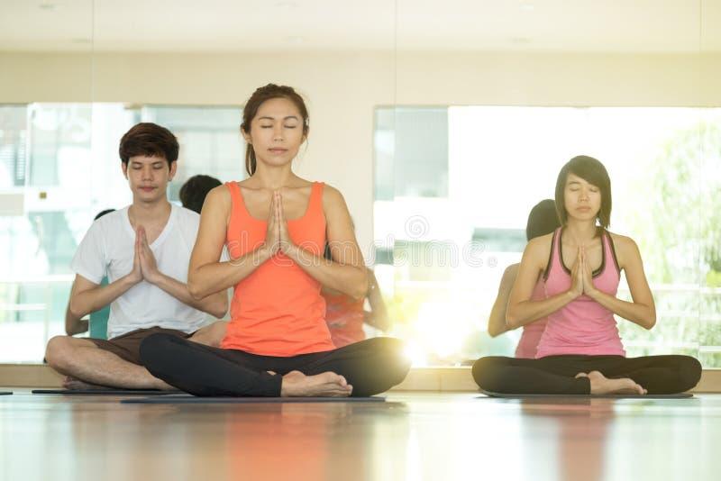 小组亚裔在namaste岗位的人民训练瑜伽室内类 免版税库存照片