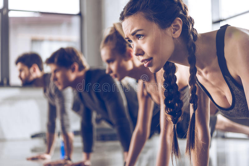 小组做俯卧撑或板条的运动服的运动青年人在健身房 免版税库存图片