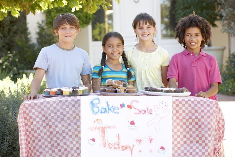 小组儿童举行烘烤销售 免版税库存照片