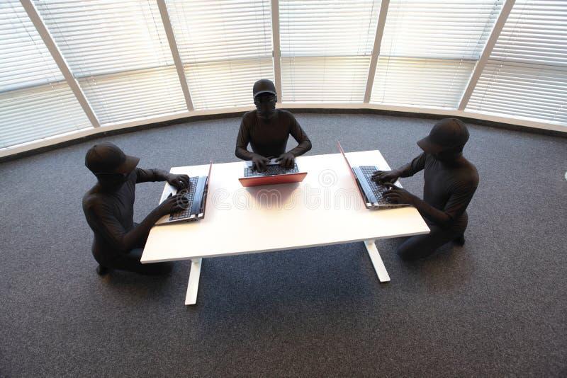 小组匿名黑客与计算机一起使用在办公室 免版税库存图片