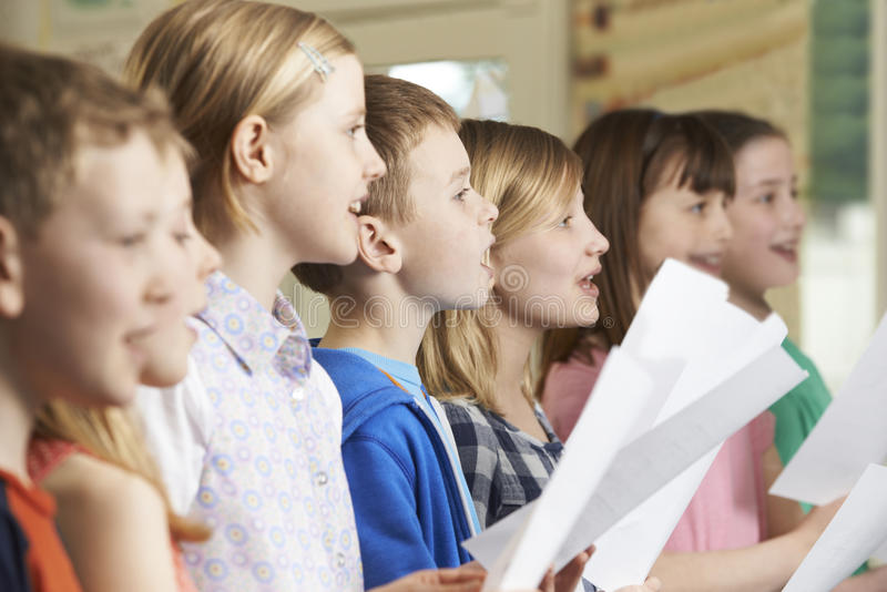 小组唱歌在学校合唱团的小学生 库存图片