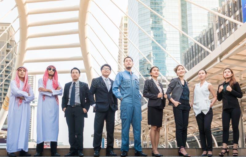 小组商人国际性组织有阿拉伯人、工程师、商人会议与日落和城市背景 免版税库存图片