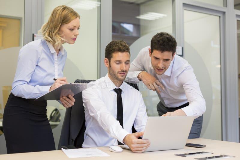 小组商人在一次会议在办公室,工作在comp 免版税库存照片