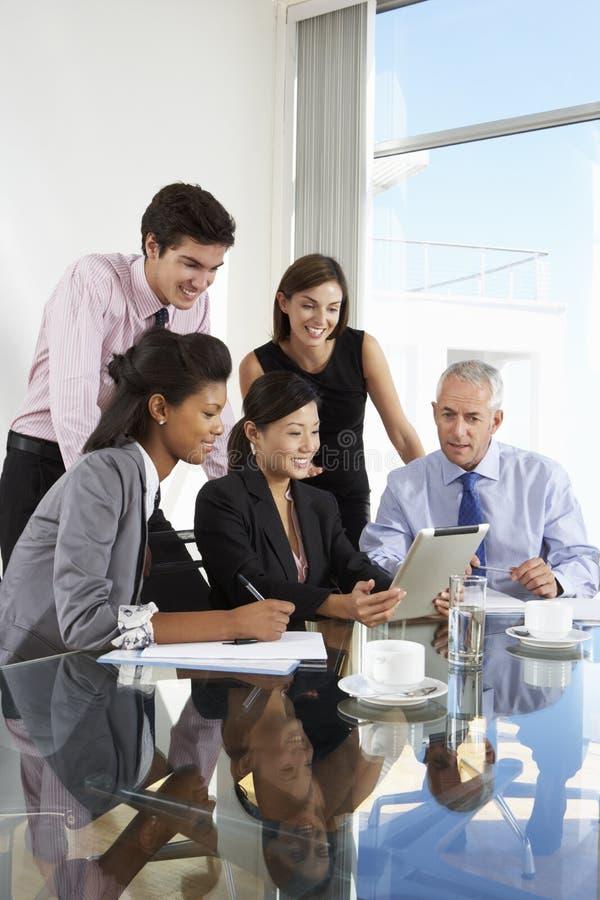 小组商人开会议在片剂计算机A附近 库存照片