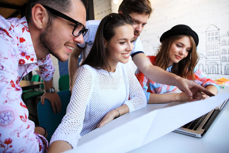 小组年轻商人,工作在他们的在coworking的空间的事业的起始的企业家 库存照片
