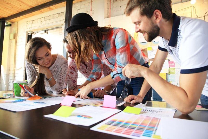 小组年轻商人,工作在他们的在coworking的空间的事业的起始的企业家 图库摄影