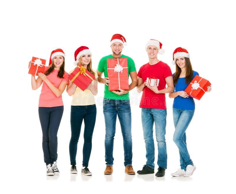 小组圣诞节帽子的微笑的朋友 免版税图库摄影