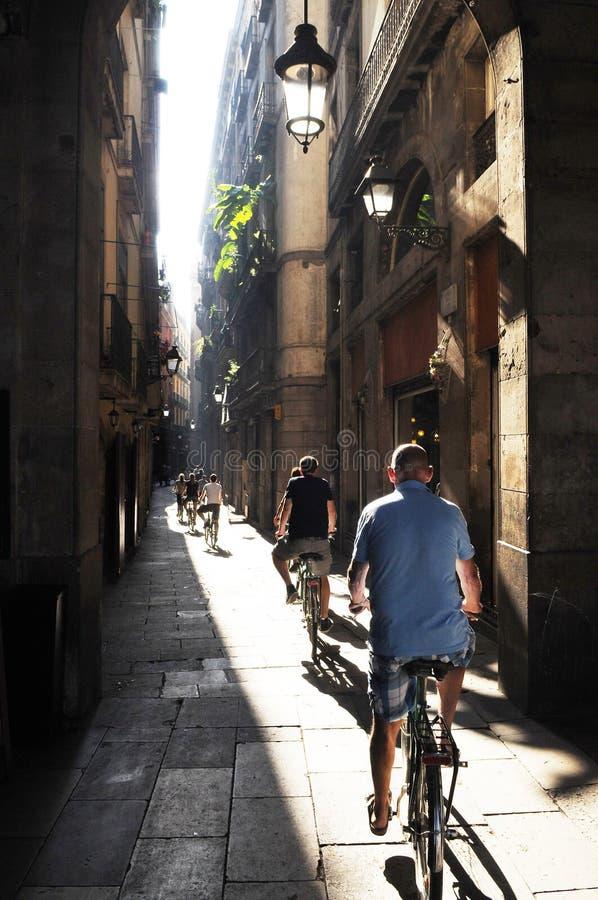 小组在一条狭窄的街道巴塞罗那上的骑自行车者 库存照片