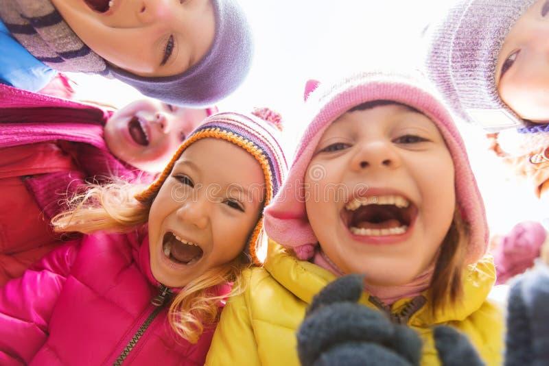 小组在圈子的愉快的儿童面孔 免版税图库摄影