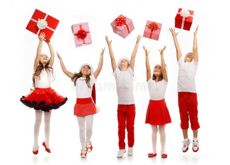 小组在圣诞节帽子传染性的礼物的愉快的孩子 免版税库存照片