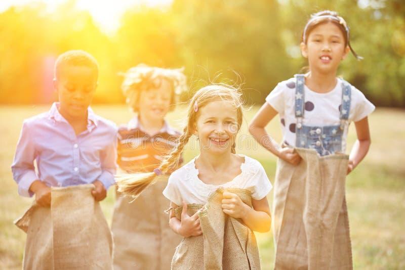 小组在套袋跑的孩子 图库摄影