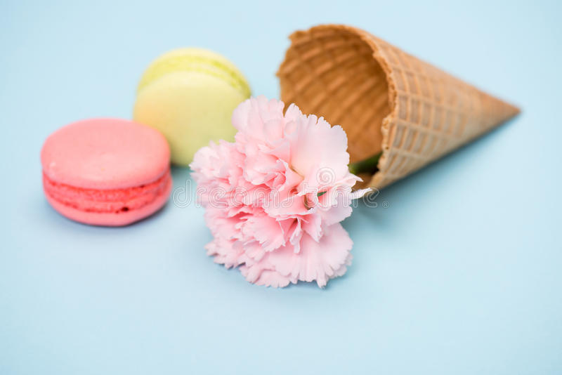 小组在奶蛋烘饼锥体和桃红色花的手工制造macarons蓝色表面上 免版税图库摄影