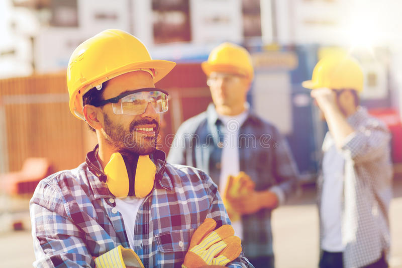 小组在安全帽的微笑的建造者户外 免版税库存照片